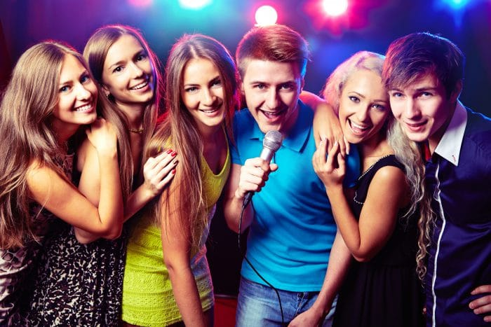 bigstock-Young-people-singing-into-micr-52313446